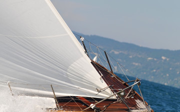 Bow of a sailing boat over the blue waves